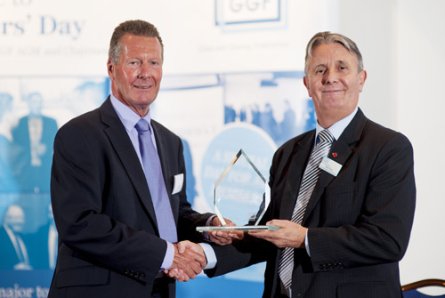 Brain Baker (left) receives the award from Nigel Rees