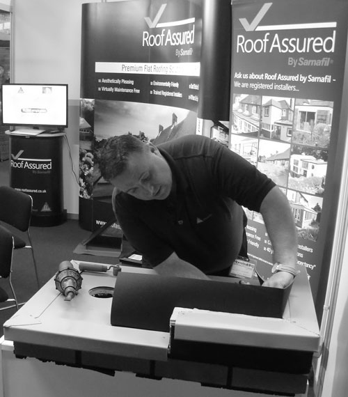 Nick Spooner, field technician, Sika Sarnafil, demonstrates the installation of the Sarnafil single ply membrane on the Roof Assured by Sarnafil stand at the Homebuilding & Renovating Show 2015, Harrogate
