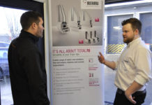 Sam Tynan discussing Rehau's Total70 product with a customer at a trade counter
